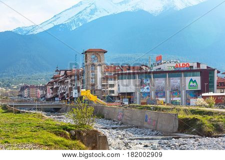 Bansko, Bulgaria April 14, 2017: Spring view with river Glazne, mountains landscape, Bansko Mall and house tower