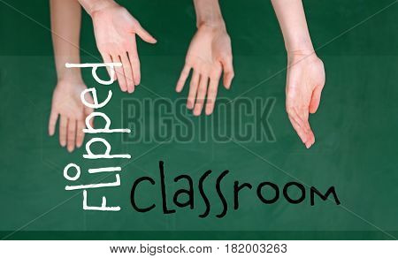 Flipped classroom concept. Inversed children's hands on blackboard background