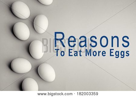 Raw eggs on gray background. Text REASONS TO EAT MORE EGGS