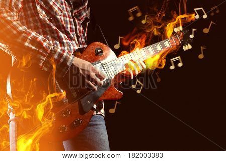 Young man playing electric guitar and fire surrounding instrument on dark background