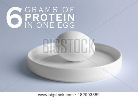 Plate with raw egg on light background. Text SIX GRAMS OF PROTEIN IN ONE EGG