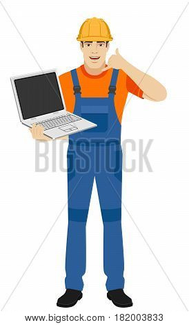 Call me! Builder holding laptop notebook and showing a call me sign. Full length portrait of builder in a flat style. Vector illustration.