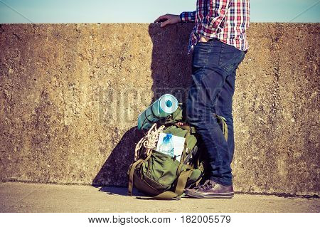 Man tourist backpacker outdoor with backpack on grunge wall. Adventure summer tourism active lifestyle. Young guy tramping