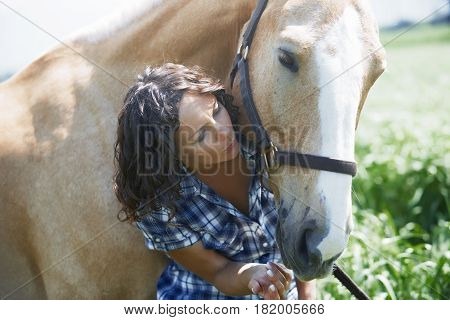Woman and horse together at paddock. Horizontal photo