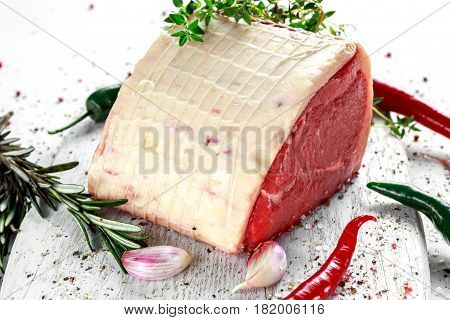 a pieces of fresh raw meat, beef slab, decorated with greens and vegetables