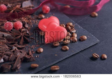 Dark chopping chocolate black roasted coffee beans red berries red chocolate with heart shape anise spice on slate board over black background. Chocolate dessert confectionery and sweets concept