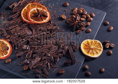 Dark chopping chocolate black roasted coffee beans dried lemon slices with spices anise on slate board over black textural background. Chocolate dessert confectionery and sweets concept