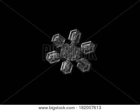 Macro photo of real snowflake: medium size snow crystal with six simple, broad arms and glossy relief surface. Black and white version. Snowflake isolated on black background.