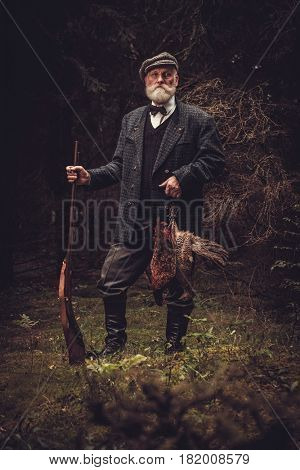 Senior hunter with a shotgun and pheasants in a traditional shooting clothing