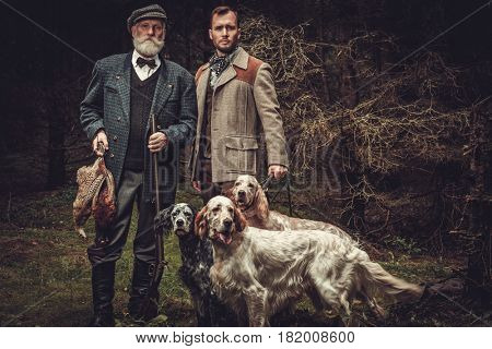 Two hunters with dogs and shotguns in a traditional shooting clothing.