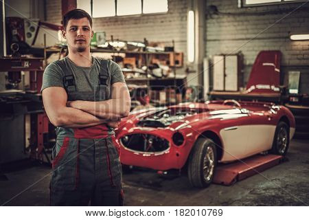 Mechanic in classic car restoration workshop
