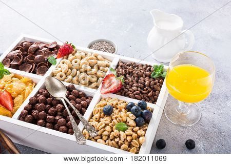 Milk jug and variety of cold quick breakfast cereals with berries in white wooden box, healthy eating concept.