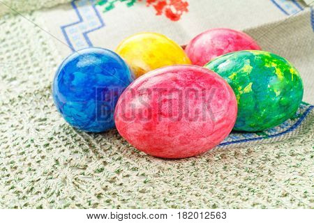 Painted colorful Easter eggs on a fabric tablecloth