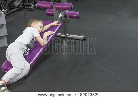 Tired Bored upset little boy in gym.