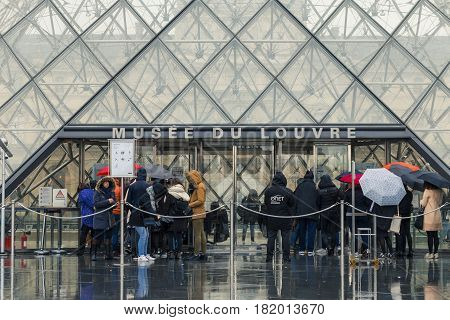 Paris, France - March 2017. People Waiting In A Queue For Entering The Louvre Museum. Tourists Walki