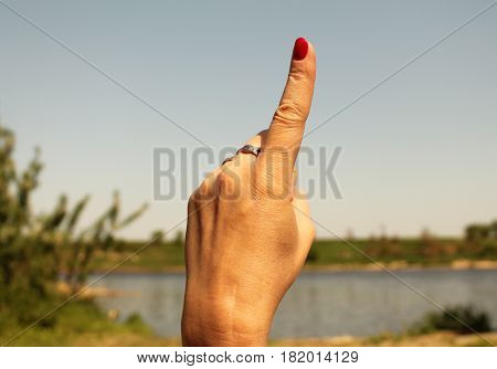 Number one sign. Woman hand with the index finger pointing up against the backdrop of summer water