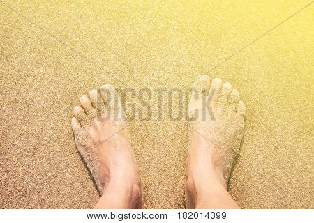 Concept of tropical relaxation. Barefooted female feet on the sand. Vintage Filter