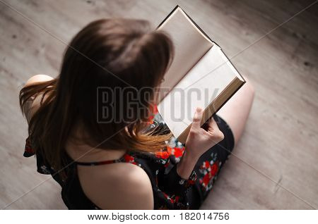 A young girl is sitting in a bright room and reading a book