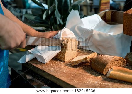 Male hands cutting wheaten bread on the wooden board in breakfast time in hotel. selective focus