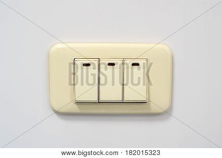 Electrical beige rocker light switch with three keys on wall