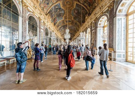 VERSAILLES FRANCE - May 07 2016 : Many tourist visiting Hall of Mirrors in Versailles palace in France. Versailles palace is the palace's most celebrated room. Setting for many of the ceremonies.