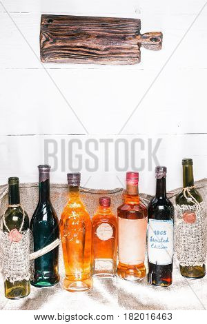 Row of various vintage wine and brandy bottles on burlap. White wood background. Rustic cutting board as title. Retro style. Top view