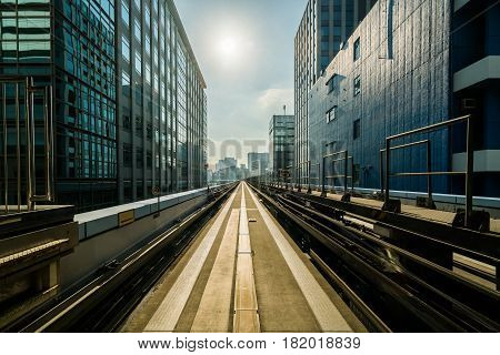 Front view of train in modern city. Straight rail with city buildings background. Transportation by train and railroad concept.