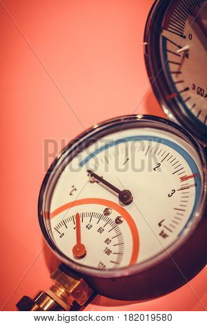 Close up shot of a pressure gauge on a red background.