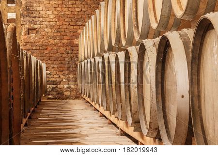 This photo shows close-up of wooden wine barrels.
