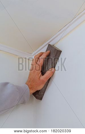 plastering man hand sanding the plaste in drywall seam plasterboard sanding the wall
