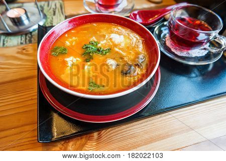Asian cuisine - Tom kha kai or Thai coconut soup with chicken meat rice mushrooms ginger and lemongrass in red bowl. Close up.