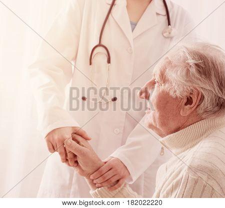 the smile elderly man with doctor indoor