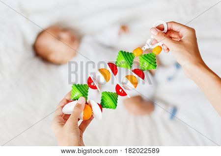 Woman holding baby's first toy - colorful rattle garland toy. Little kid on background.