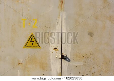 Close up of yellow high voltage sign on grey metal wall
