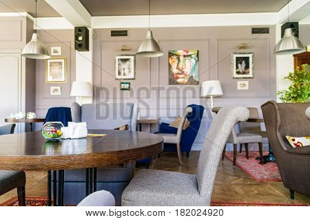 Interior of restaurant with grey chairs, round wooden table, painting and photos in frames on wall