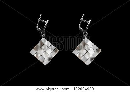 Nacre chess earrings isolated on black background