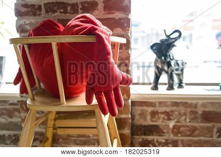 Close up red cushion in shape of heart on wooden chair