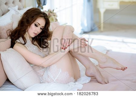Beautiful sexy lady in elegant white robe. Close up fashion portrait of model indoors. Beauty brunette woman with attractive body in lace lingerie. Female ass in underwear. Closeup naked girl