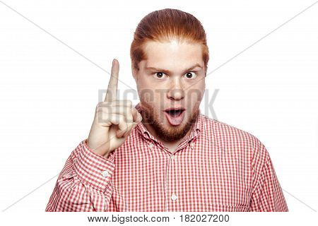 Excited man pointing a great idea happy bearded readhead businessman with red shirt and freckles looking at camera. studio shot isolated on white.