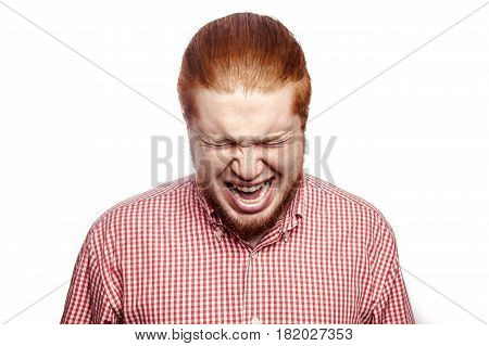 Screaming angry bearded readhead businessman with red shirt and freckles looking at camera. studio shot isolated on white.