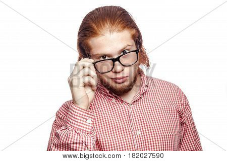 thoughtful thinking bearded readhead businessman with red shirt and freckles holding glasses and looking at camera . studio shot isolated on white.