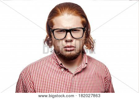 Thoughtful thinking bearded readhead businessman with red shirt and freckles and glasses looking at camera. studio shot isolated on white.