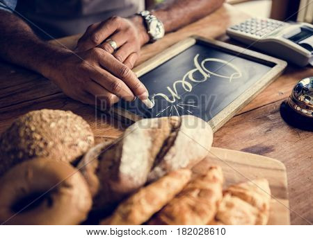 Man writing blackboard about service hour of bakehouse