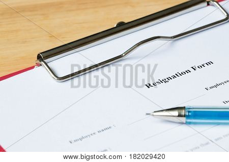 Resignation form in red file on wood desk background