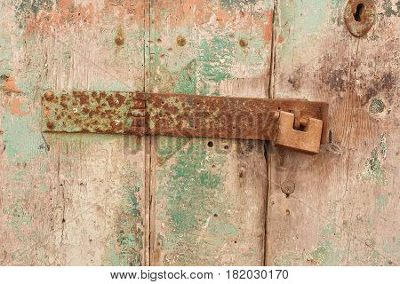 Rusty hinge of a wooden door with green paint