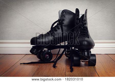 men's roller skates on hardwood floor with grey wall