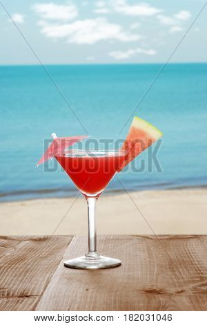 watermelon martini by the beach with fruit slice