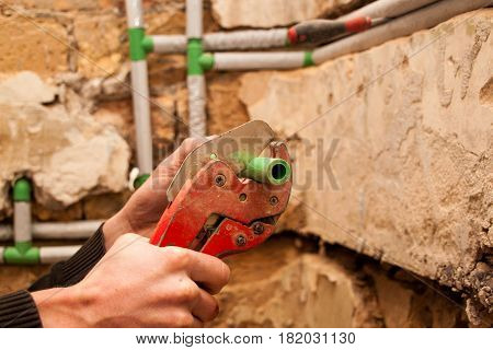 Plumber Sets The Water Pipes In The Bathroom, With The Shortened Pipe Scissors Pipe