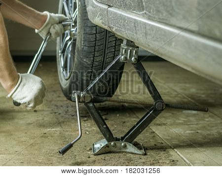 Male hands spun the wheel of the car in the garage. Replacement rear wheel vehicle mechanic in the garage.