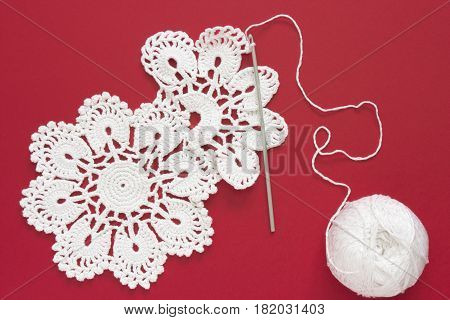 White vintage crochet doily. Cotton yarn for knitting and crochet hook